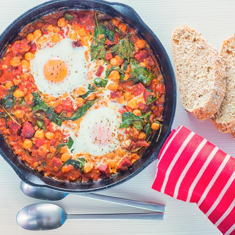 Overhead square image of baked chickpeas with tomato and eggs served and cooked in a cast iron skillet served with seeded bread