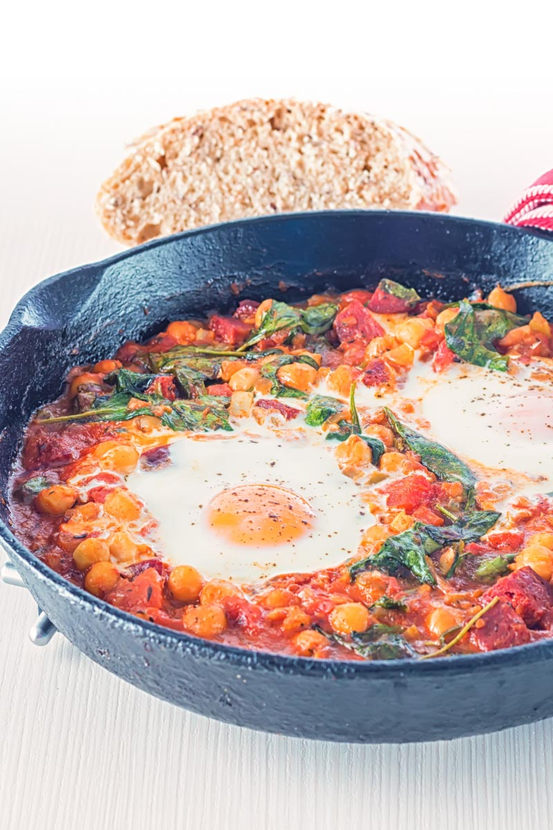 Portrait square image of baked chickpeas with tomato and eggs served and cooked in a cast iron skillet served with seeded bread