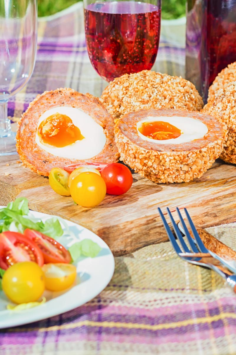 Cut open baked scotch egg in a picnic setting with tomatoes on a purple tartan picnic blanket on a sunny day