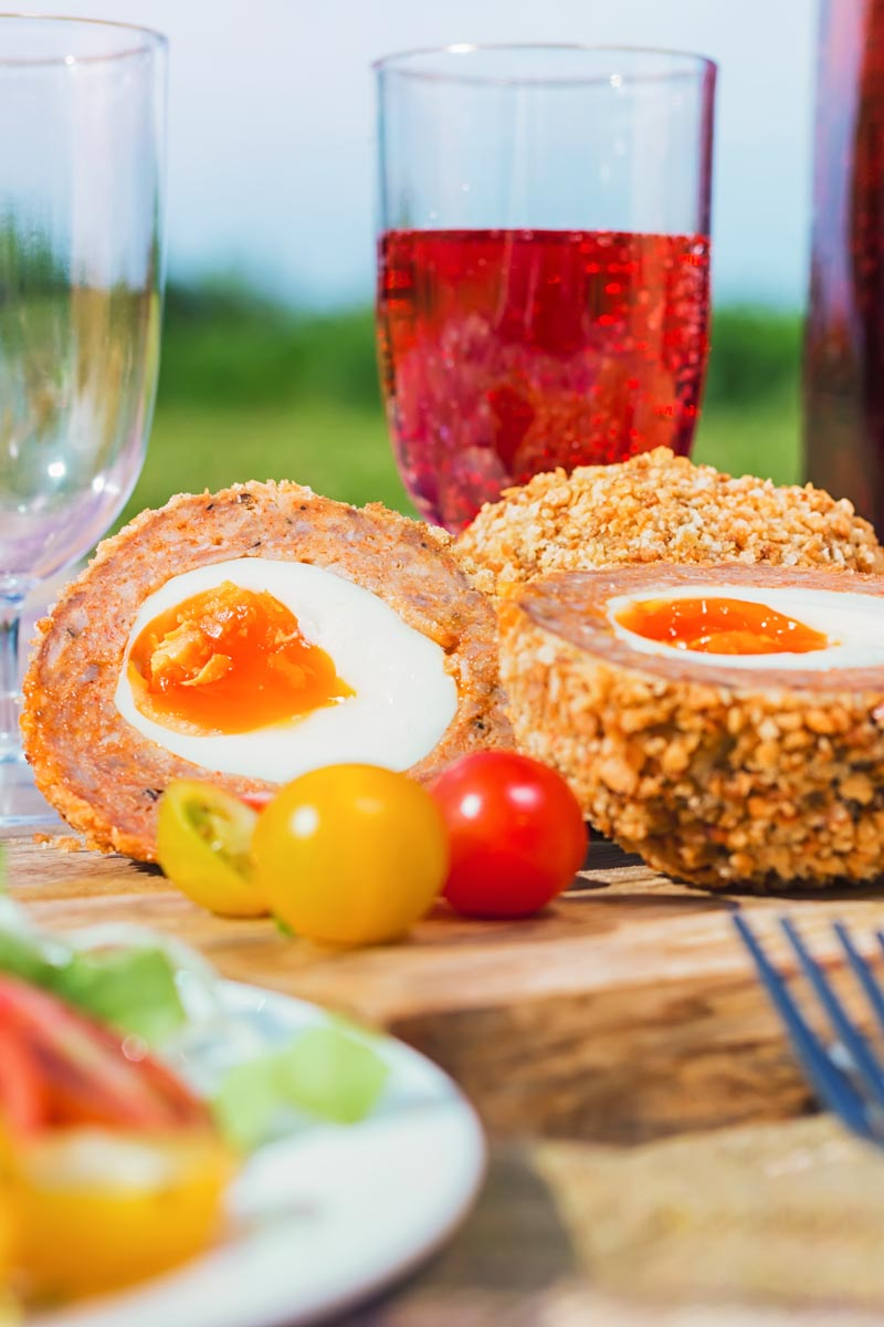 Tall close up image of a baked scotch egg with a perfect jammy yolk in a picnic setting