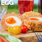 Tall close up image of a baked scotch egg with a perfect jammy yolk in a picnic setting with text