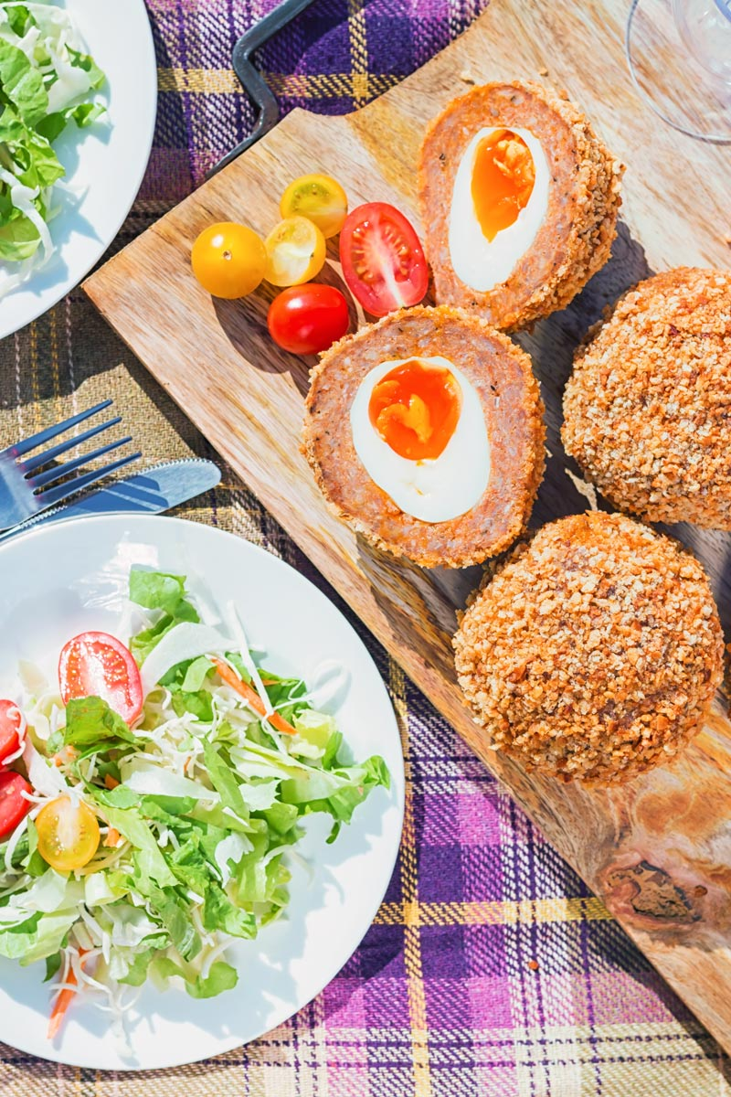 Tall overhead image of baked scotch eggs with one cut open showing jammy yolk in a picnic setting with a green side salad