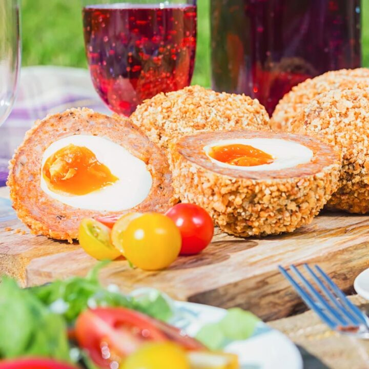 Close up square image of baked scotch eggs with one cut open in a picnic setting
