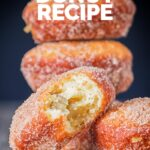 Portrait Image of cinnamon sugar coated donuts with a bite out of one cooked from a basic donut recipe with text
