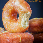 Portrait Image of lemon glazed ring donuts with a bite out of one cooked from a basic donut recipe with text