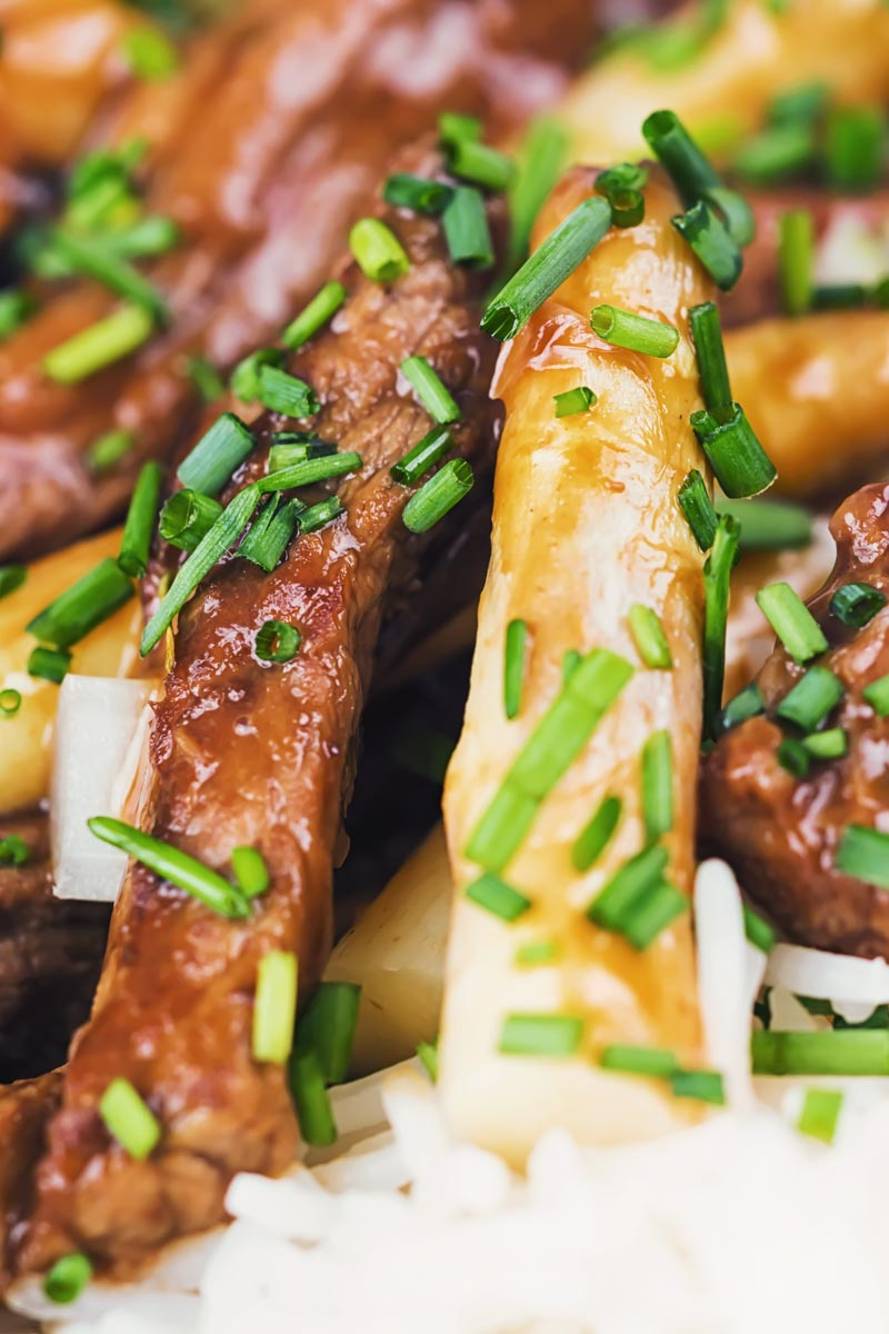 Tall extreme close up image of beef with oyster sauce and white asparagus in a white bowl with herbed rice