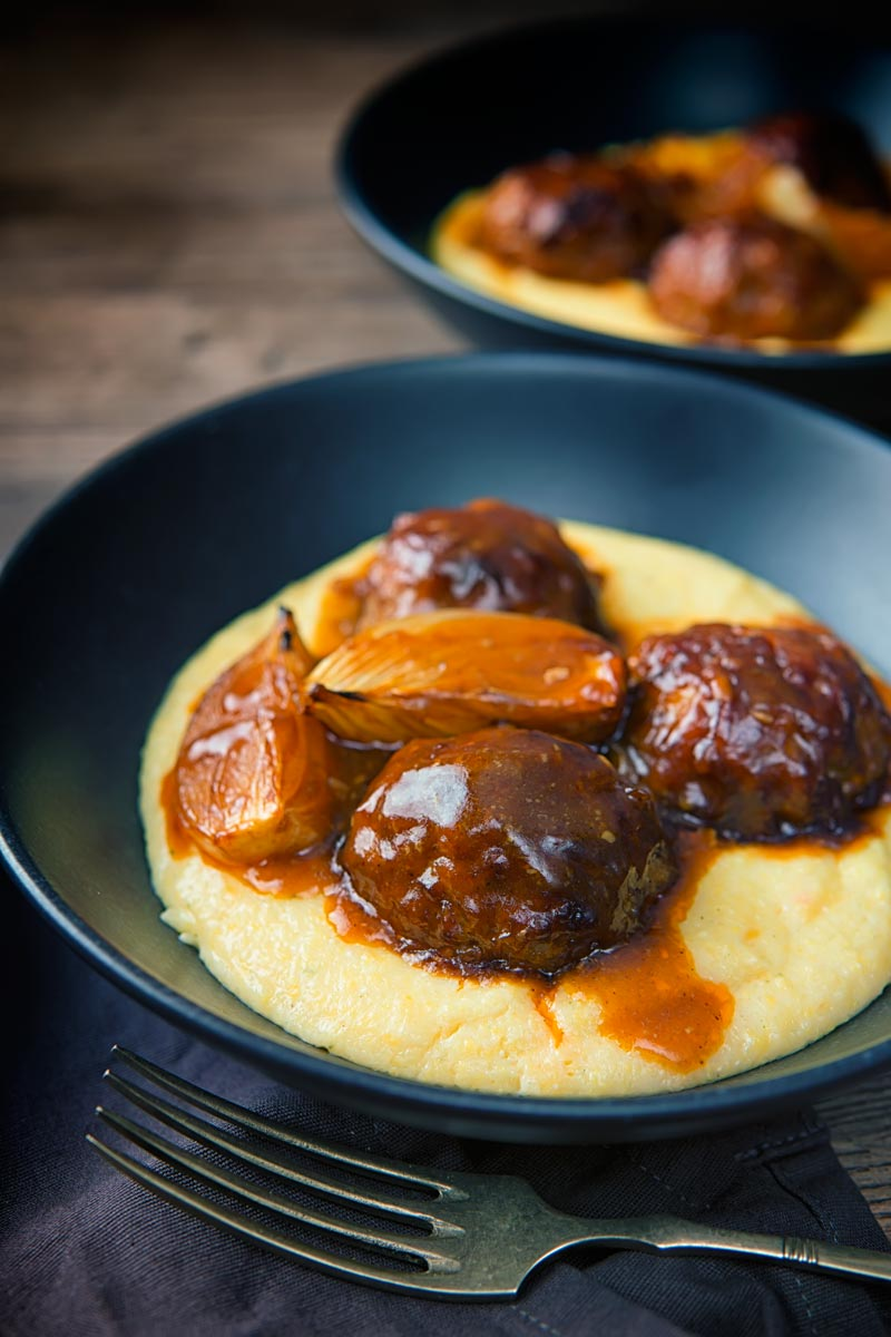 Portrait image of pork meatballs, onion wedges and a beer sauce served on polenta in two black bowls with a vintage fork and dark linen