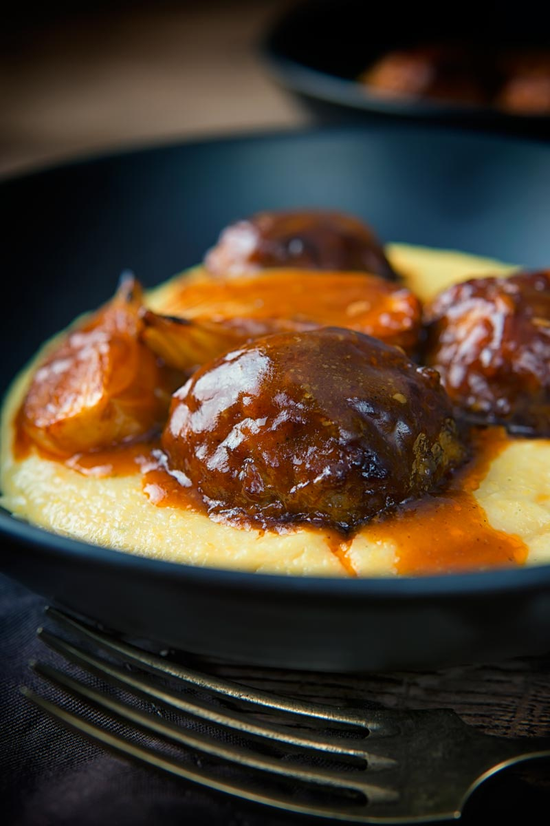 Portrait close up image of pork meatballs, onion wedges and a beer sauce served on polenta in a black bowl with a vintage fork and dark linen