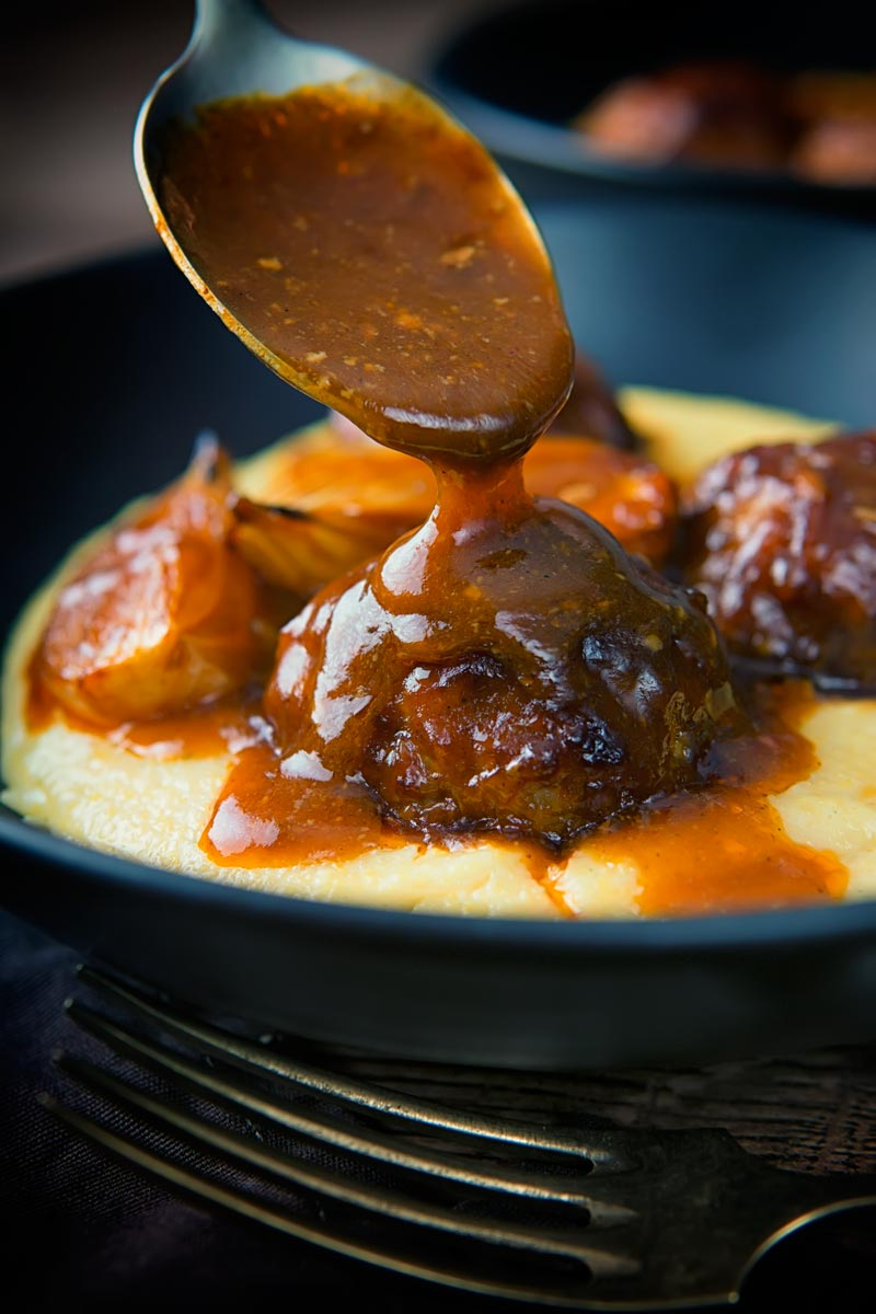 Portrait close up image of beer sauce poured over pork meatballs on polenta in a black bowl with a vintage fork and dark linen