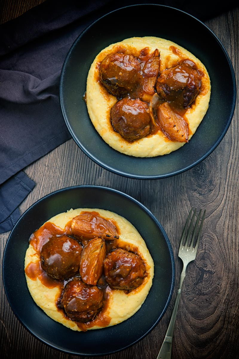 Portrait overhead image of pork meatballs and onion wedges with beer sauce on polenta served in two black bowls with a vintage fork and dark linen