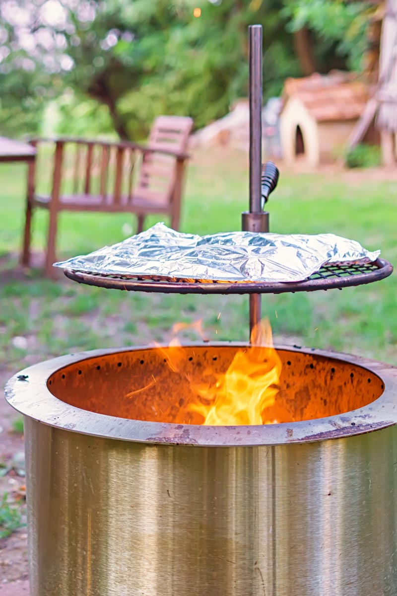 Portrait image of foil packets baking over a fire pit on a summers day