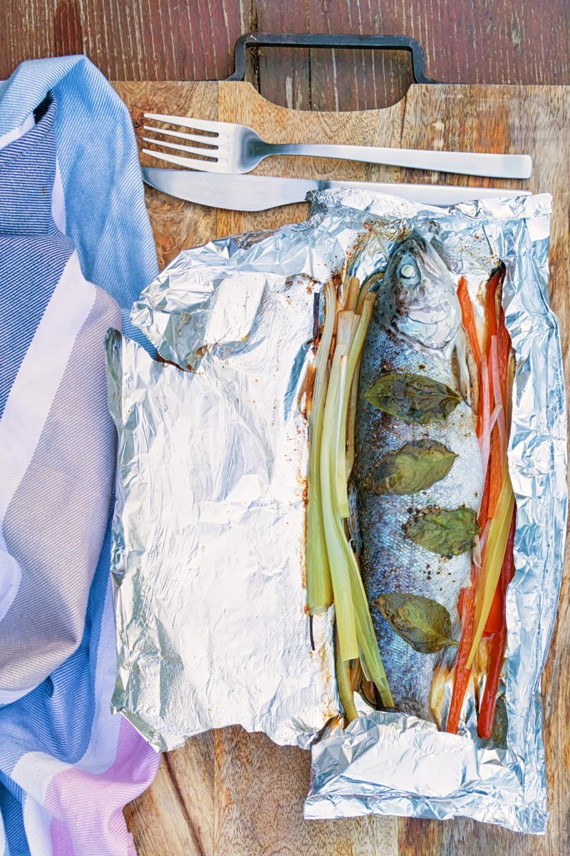 Portrait image of baked fish in foil with vegetable ribbons and basil leaves on a wooden chopping board