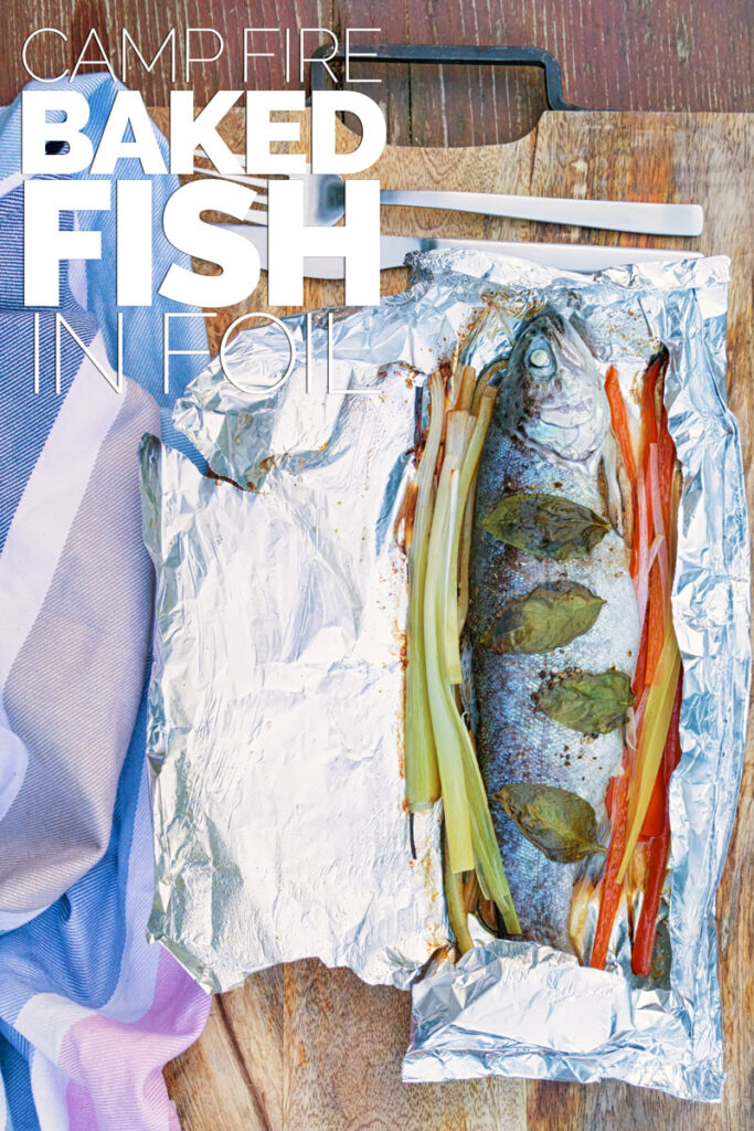 Portrait image of baked fish in foil with vegetable ribbons and basil leaves on a wooden chopping board with text