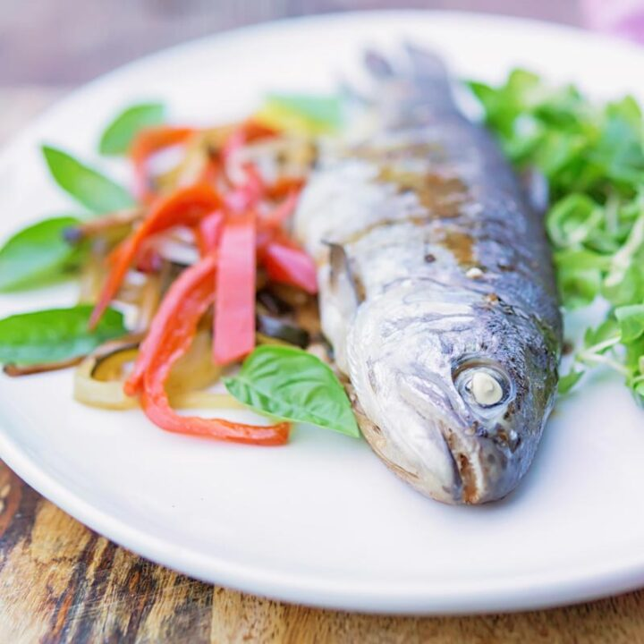 Square image of a whole cooked trout baked in foil with vegetable ribbons and side salad on a white plate