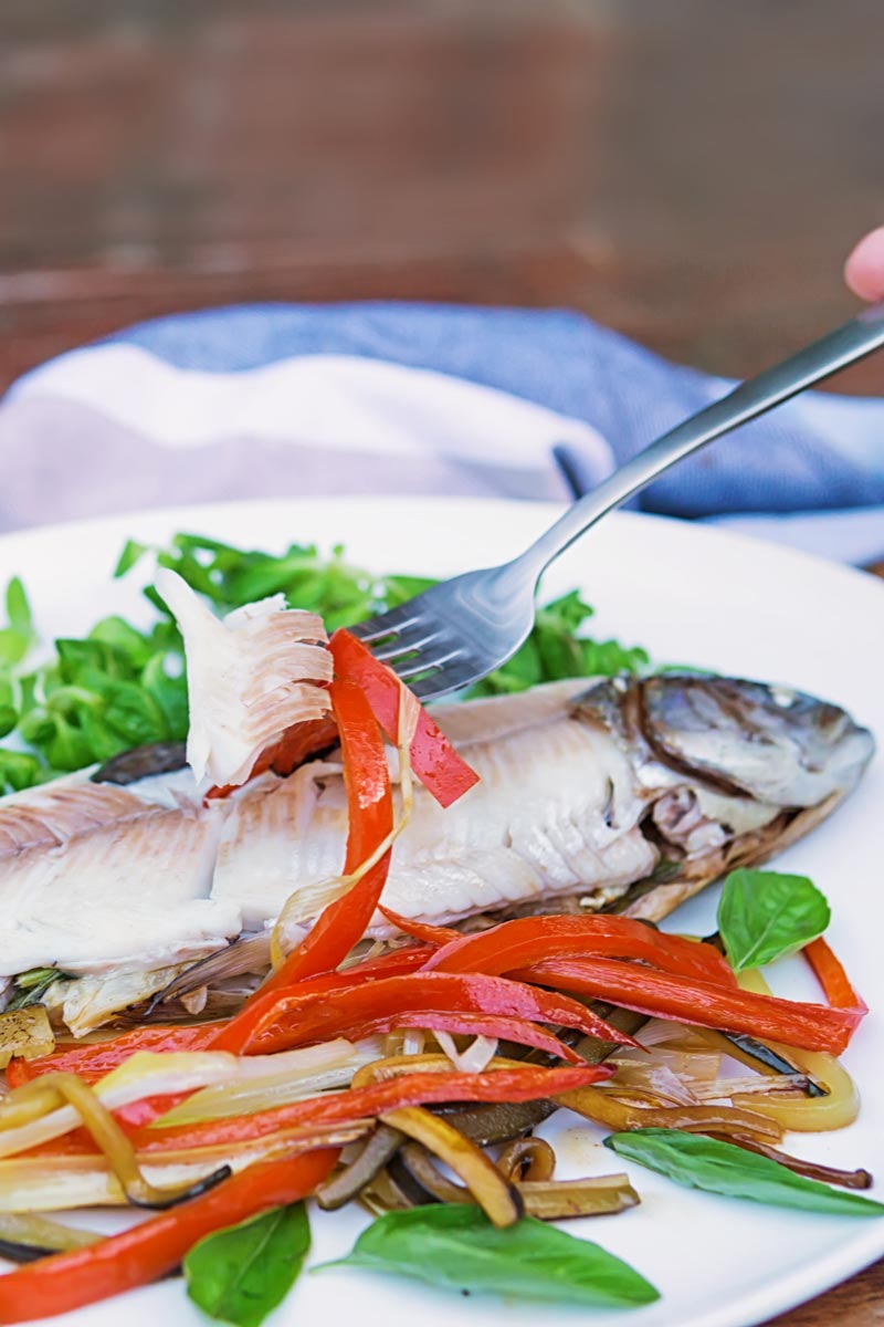 Portrait image of a fork showing the moist cooked flesh of a whole fish baked in foil with vegetable ribbons and salad