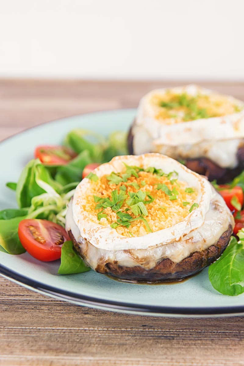 Portrait image of stuffed portobello mushrooms with goats cheese and a breadcrumb topping served with a green salad and tomatoes