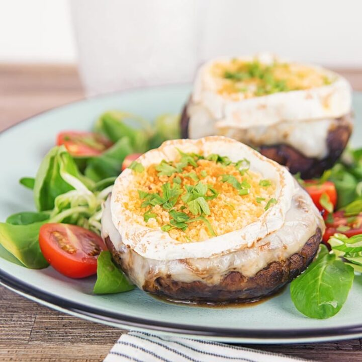 Square image of stuffed portobello mushrooms with goats cheese and a breadcrumb topping served with a green salad and tomatoes