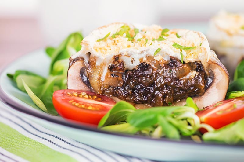 Landscape image of stuffed portobello mushrooms with goats cheese and a breadcrumb topping cut open to show a caramelised onion centre served with a green salad and tomatoes
