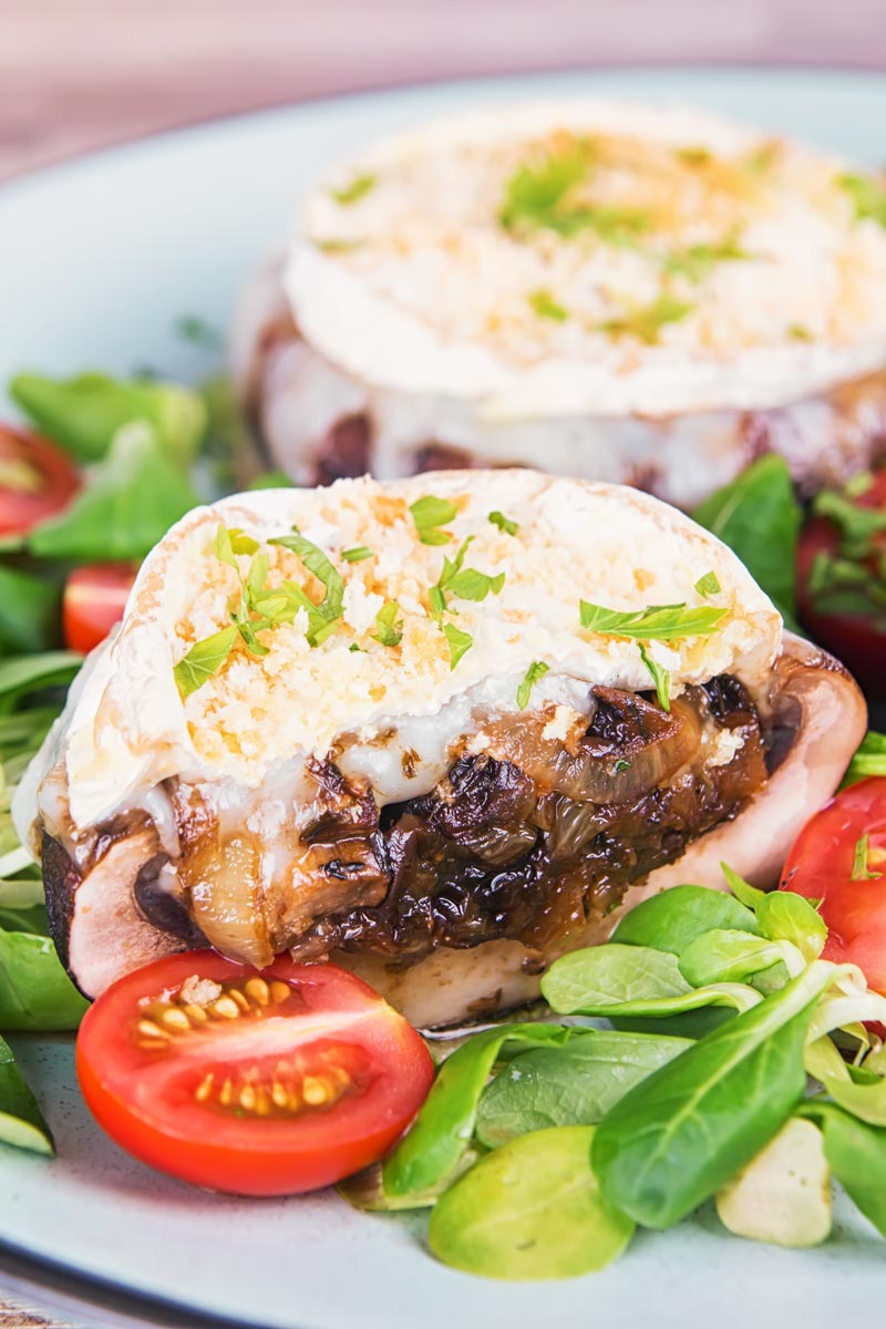 Portrait image of stuffed portobello mushrooms with goats cheese and a breadcrumb topping cut open to show a caramelised onion centre served with a green salad and tomatoes