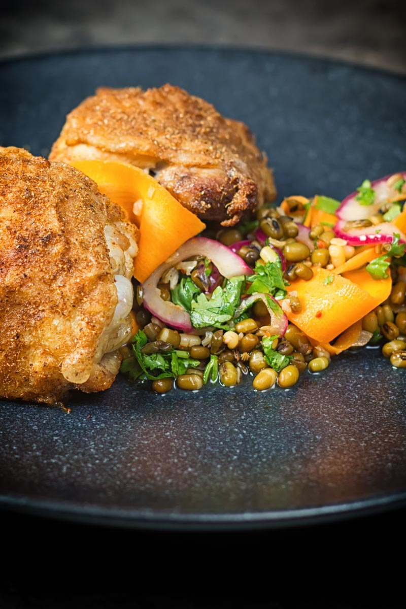 Carrot and mung bean salad on a black plate with spiced chicken thighs