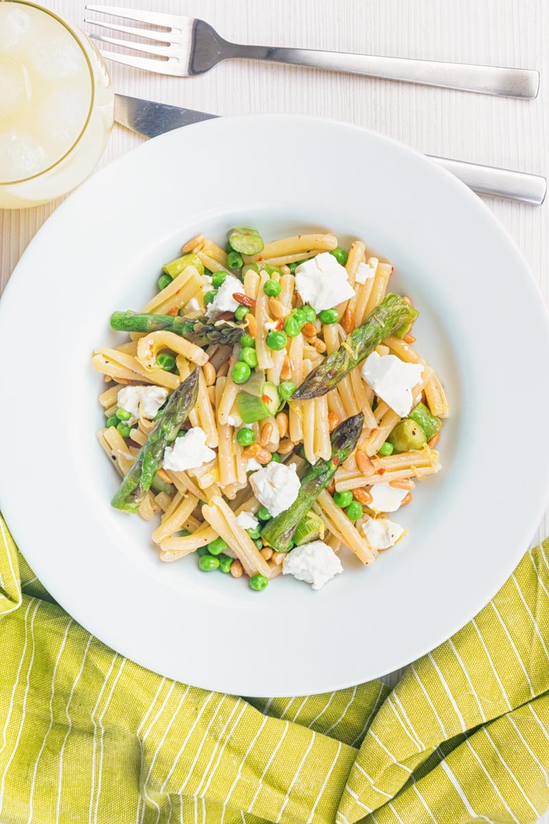 Portrait overhead image of Casarecce Pasta With Peas, Asparagus, Feta cheese and Pine Nuts with green linen