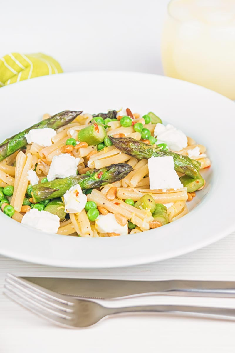 Portrait image of Casarecce Pasta With Peas, Asparagus, Feta cheese and Pine Nuts in a white bowl