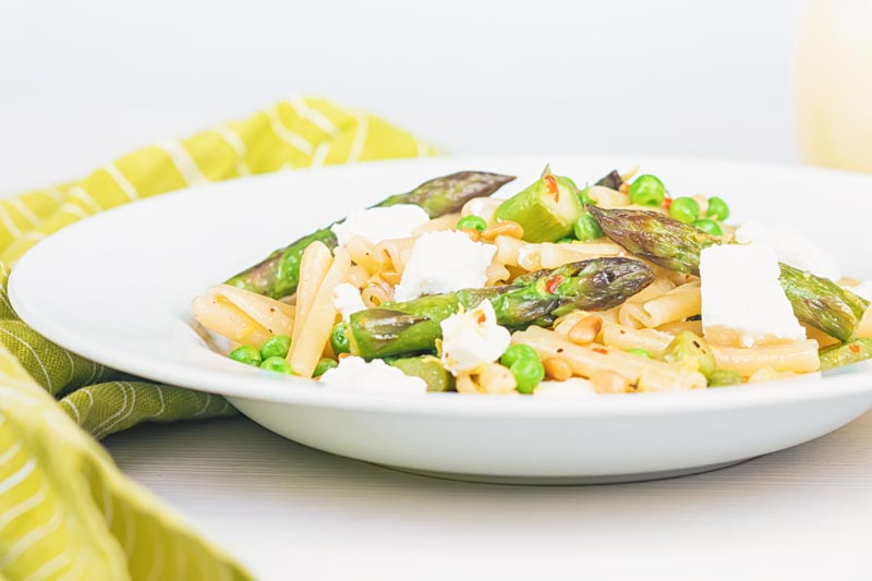 Landscape image of Casarecce Pasta With Peas, Asparagus, Feta cheese and Pine Nuts in a white bowl