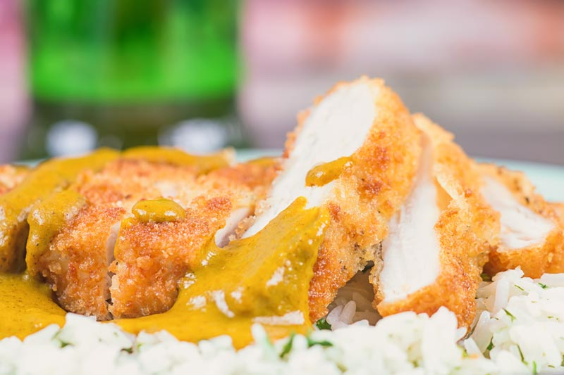 Lanscape image of chicken katsu curry sliced against a bright backdrop on a bed of white rice
