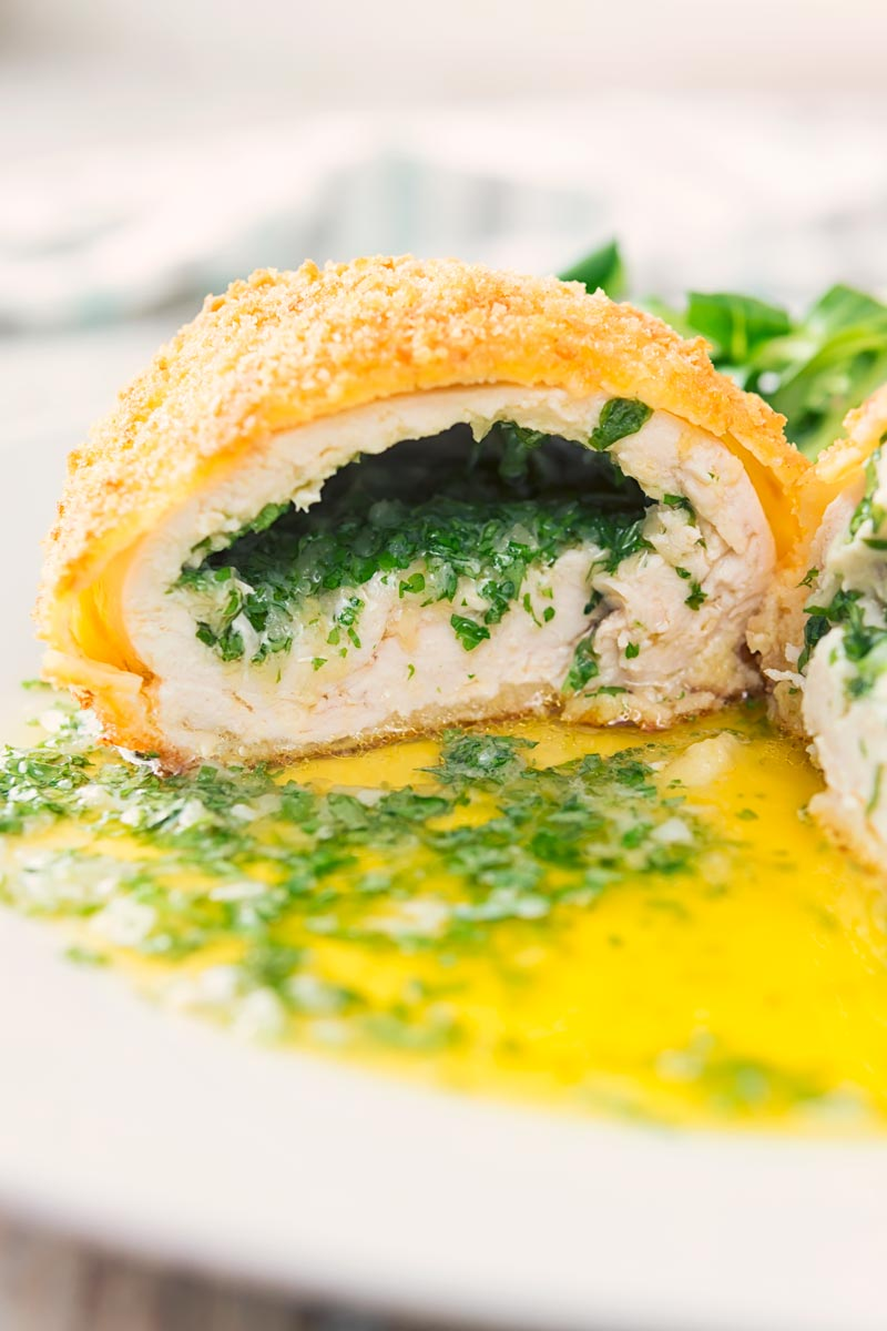 Close up portrait image of a garlic chicken Kiev cut open releasing it's garlic butter and parsley all over a white plate, served with a side salad and mashed potato