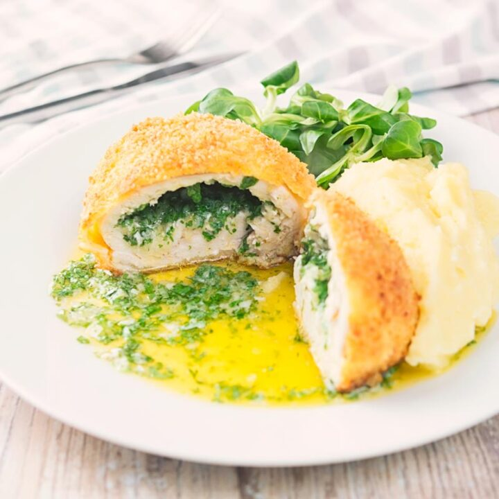 Square image of a garlic chicken Kiev cut open releasing it's garlic butter and parsley all over a white plate, served with a side salad and mashed potato