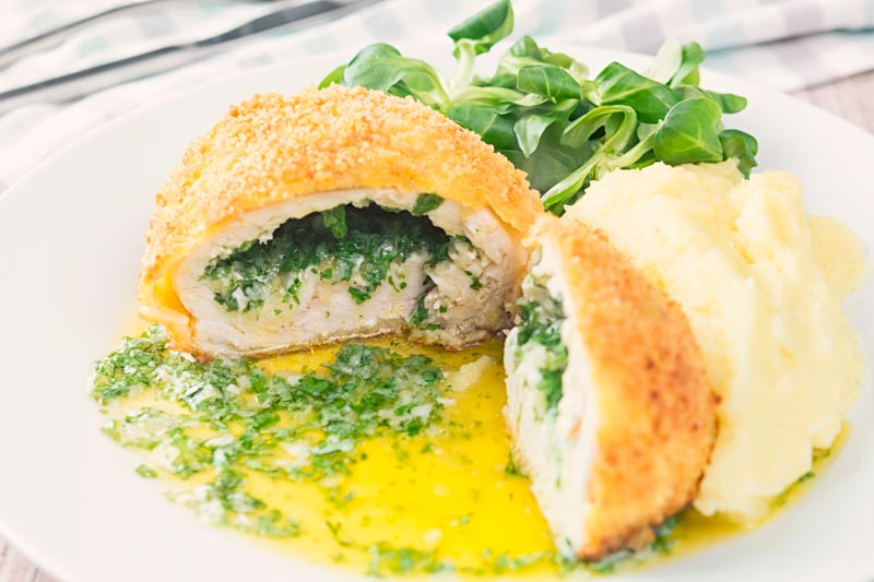 Landscape image of a garlic chicken Kiev cut open releasing it's garlic butter and parsley all over a white plate, served with a side salad and mashed potato