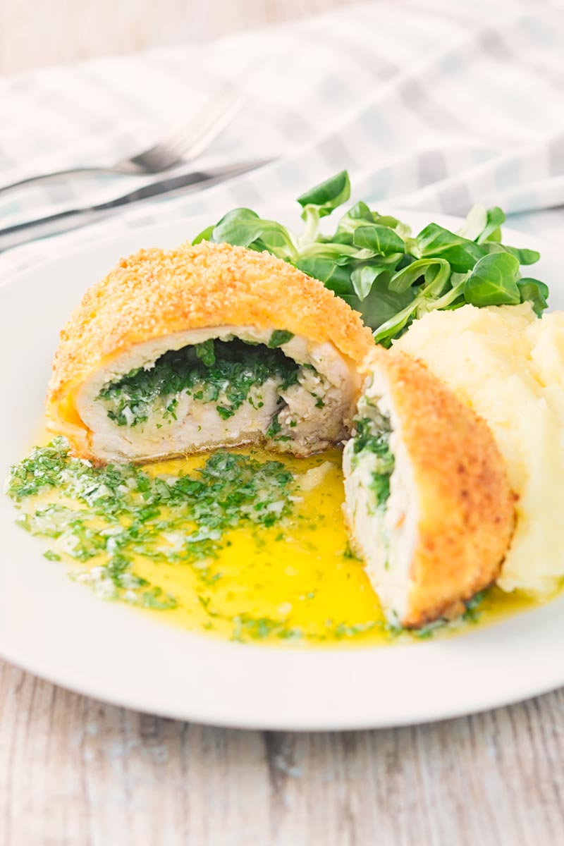 Portrait image of a garlic chicken Kiev cut open releasing it's garlic butter and parsley all over a white plate, served with a side salad and mashed potato
