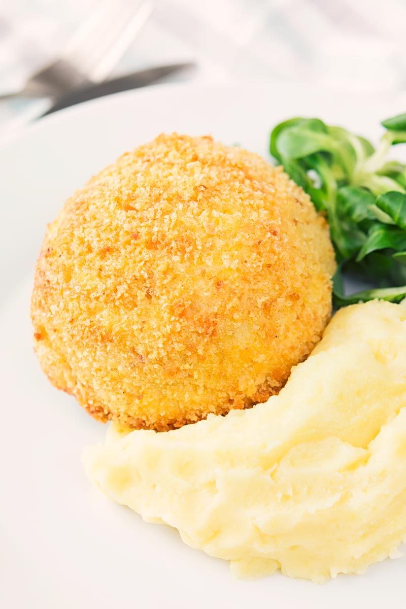 Portrait image of a crispy garlic chicken Kiev on a white plate, served with a side salad and mashed potato