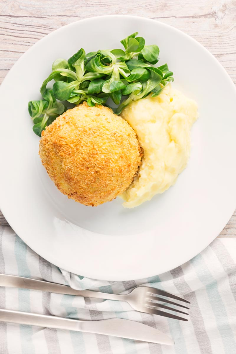 Portrait overhead image of a crispy garlic chicken Kiev on a white plate, served with a side salad and mashed potato