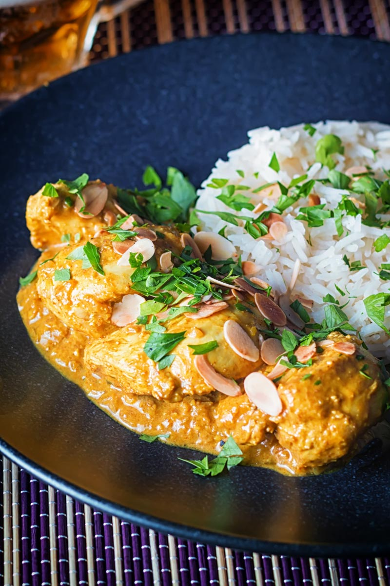 Tall image of a chicken pasanda curry with a pile of basmati rice and flaked almonds on a black plate