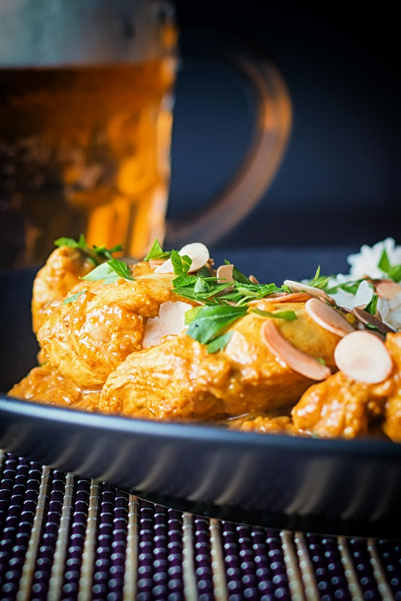Tall close up image of a chicken pasanda curry with a pile of basmati rice and flaked almonds on a black plate with a beer in the background