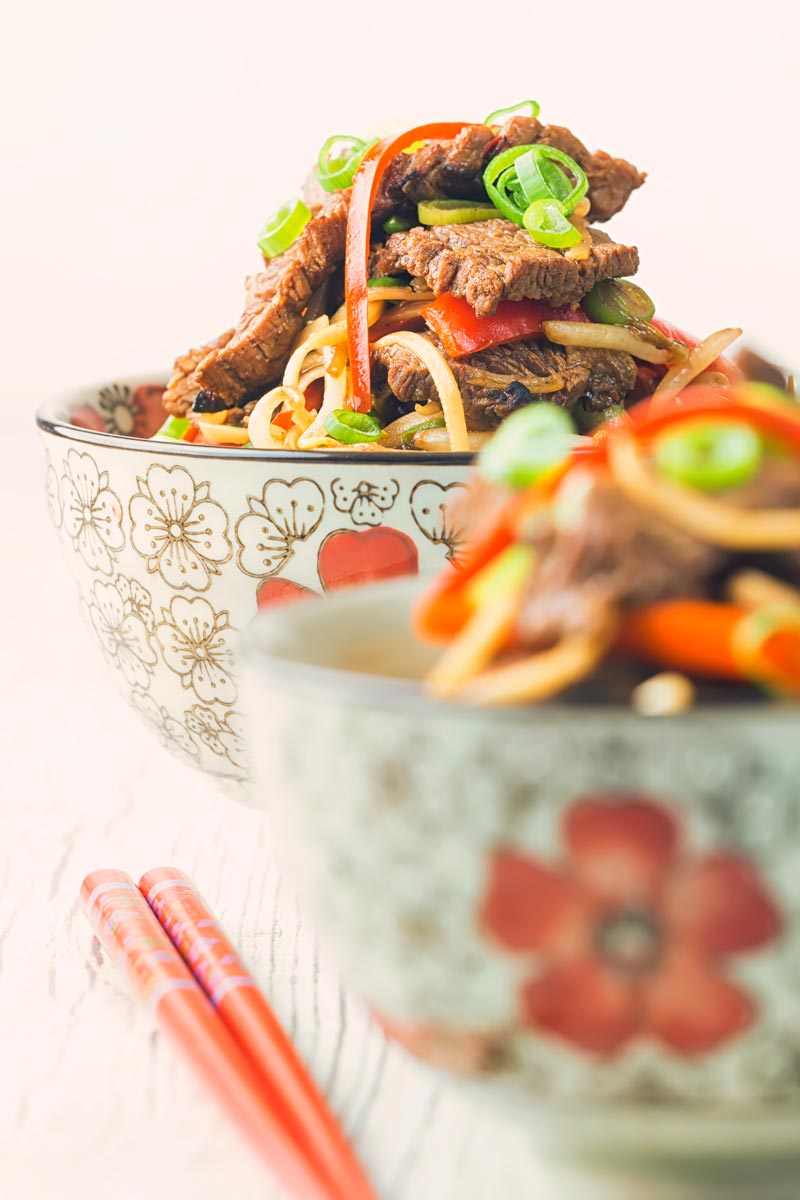 Portrait image of chili beef and noodles served in two Asian style noodle bowls decorated with a red flower with the rear bowl in focus