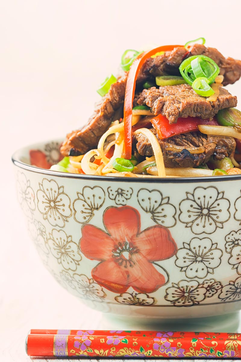 Close up portrait image of chili beef and noodles served in an Asian style noodle bowl decorated with a red flower with red patterned chop sticks
