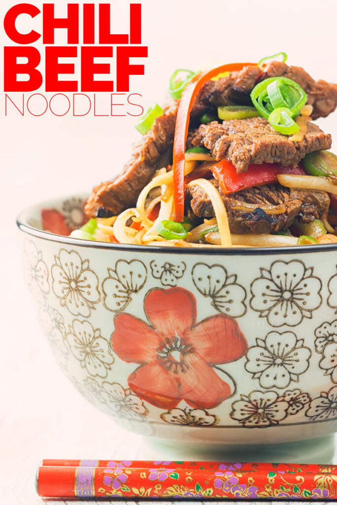 Close up portrait image of chili beef and noodles served in an Asian style noodle bowl decorated with a red flower with red patterned chop sticks with text