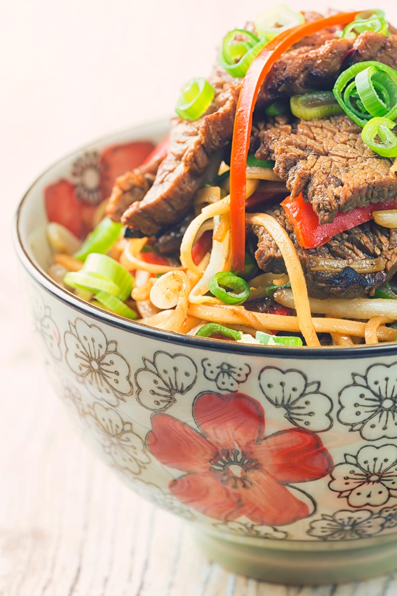Close up portrait image of chili beef and noodles served in an Asian style noodle bowl decorated with a red flower