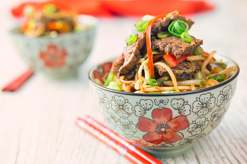 Landscape image of chili beef and noodles served in two Asian style noodle bowls decorated with a red flower