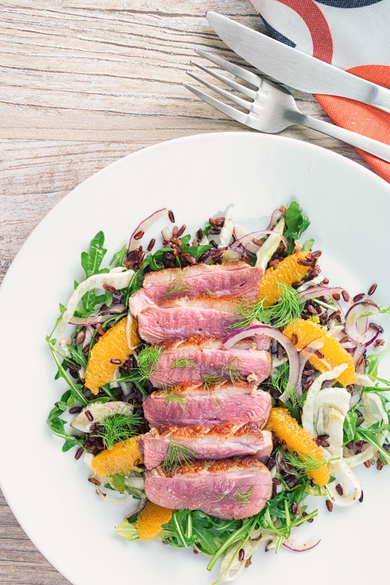 Portrait overhead image of a fennel and orange salad served with a sliced rosy pink duck breast served on a white plate