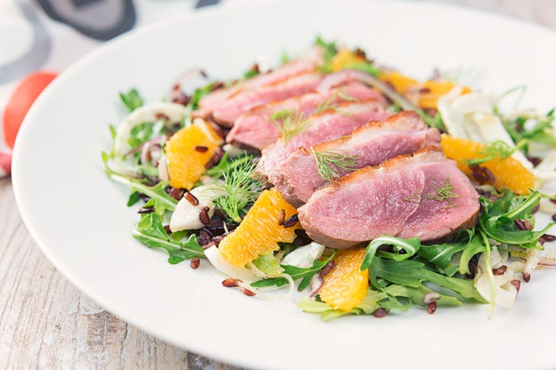 Landscape image of a fennel and orange salad served with a sliced rosy pink duck breast served on a white plate