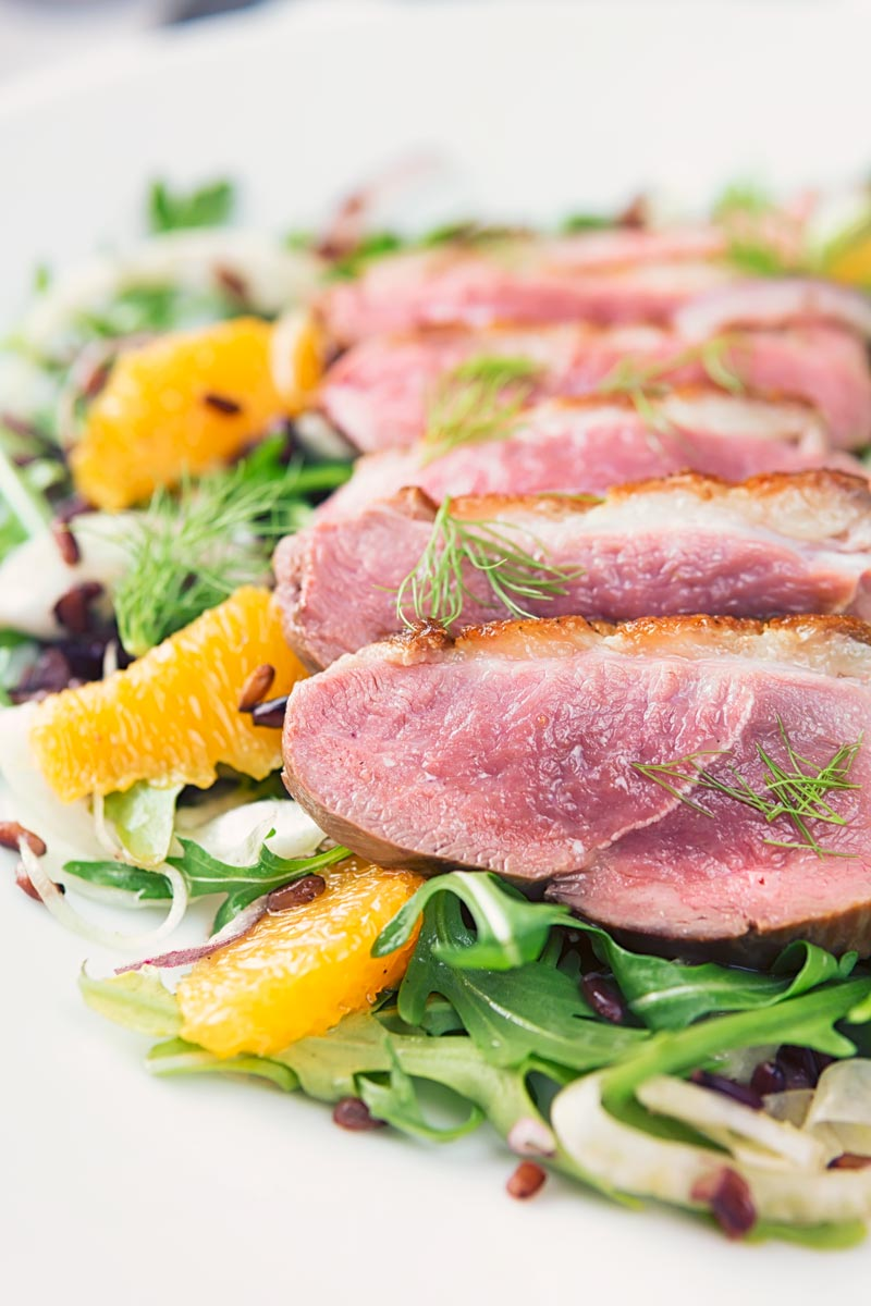 Portrait close up image of a fennel and orange salad served with a sliced rosy pink duck breast served on a white plate