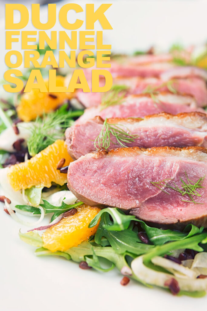 Portrait overhead image of a fennel and orange salad served with a sliced rosy pink duck breast served on a white plate with text