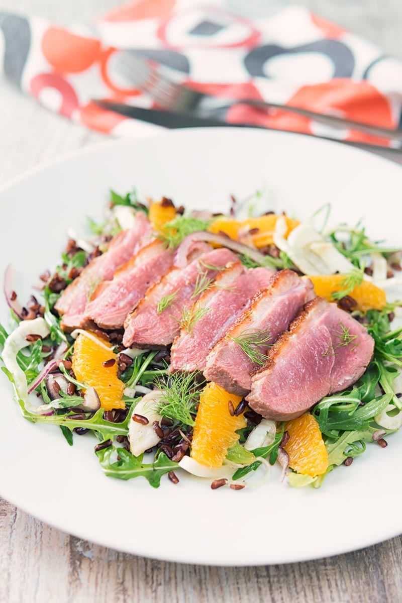 Portrait image of a fennel and orange salad served with a sliced rosy pink duck breast served on a white plate