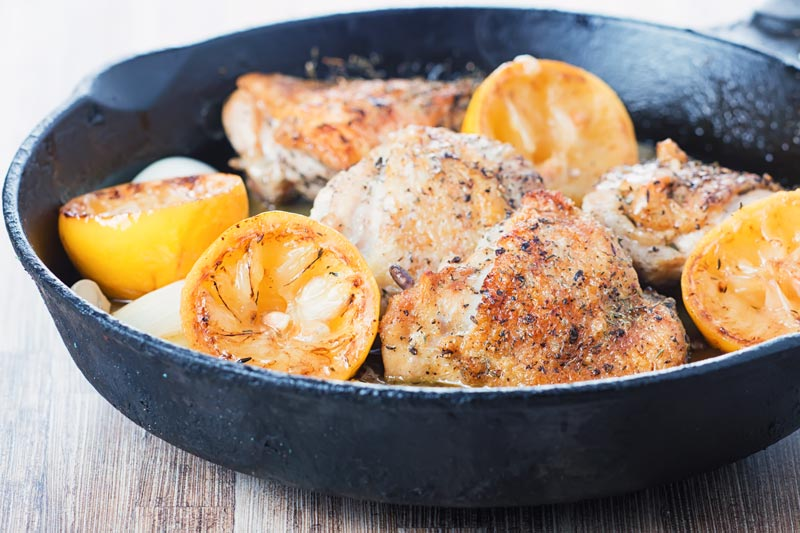 Landscape image of Garlic Lemon Chicken cooked in a cast iron skillet