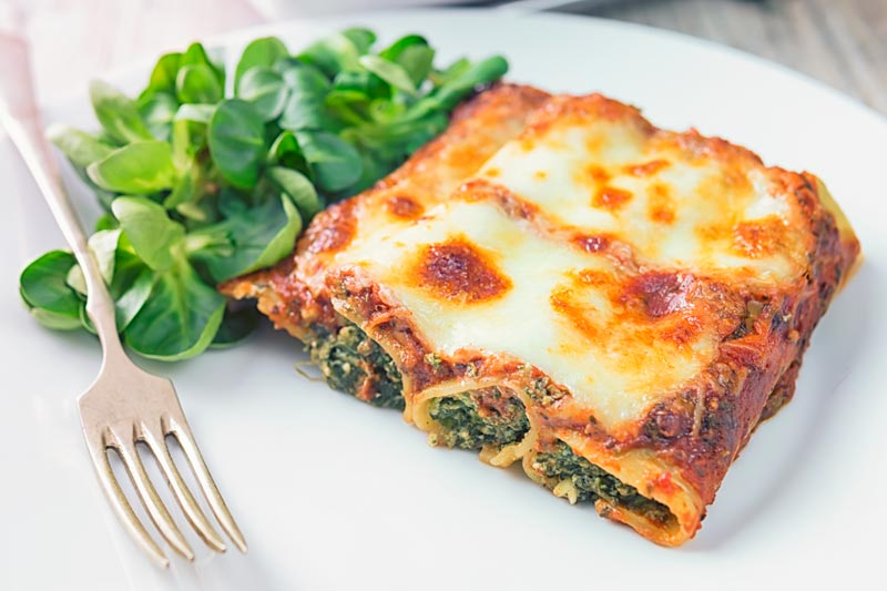 Landscape image of baked Goats' Cheese and Spinach Cannelloni on a white plate with a vintage fork and side salad
