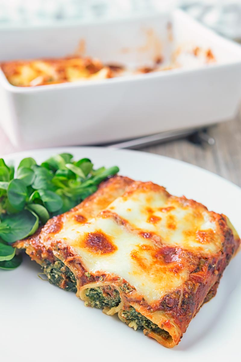Portrait image of baked Goats' Cheese and Spinach Cannelloni on a white plate with a vintage fork and side salad