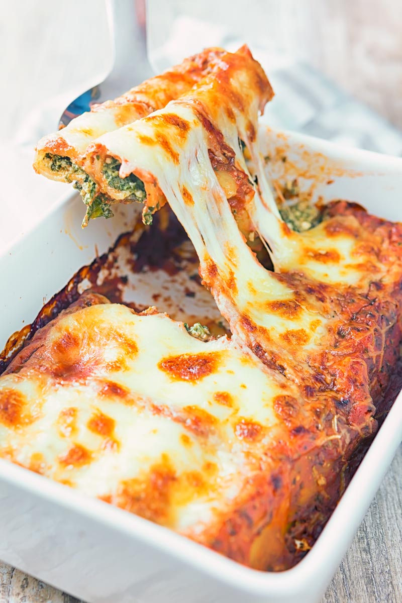 Portrait image of baked Goats' Cheese and Spinach Cannelloni in a white casserole dish being served with a cheese pull